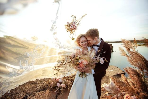 Die braut und der bräutigam nahe der hochzeitsdekoration bei einer zeremonie auf einer felsenklippe nahe dem wasser bei sonnenuntergang. schleier fliegt vom wind