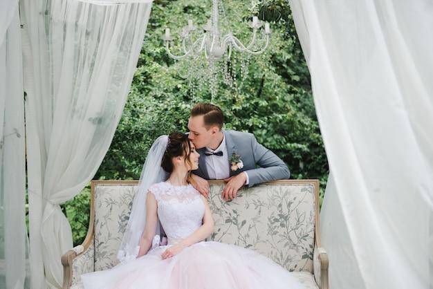 Die braut und der bräutigam sitzen auf einer schönen couch in einem pavillon im garten