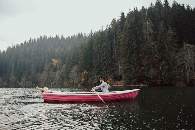 Die braut und der bräutigam sitzen zusammen in einem kleinen rosa boot auf dem see. der ehemann rollt seine frau auf dem boot.