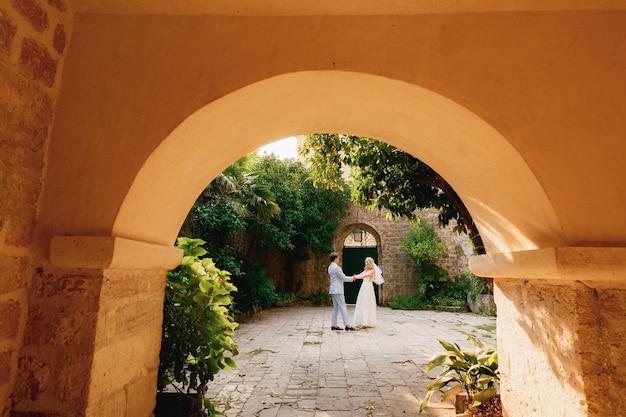 Die braut und der bräutigam tanzen und kreisen im coutryard in der altstadt von perast