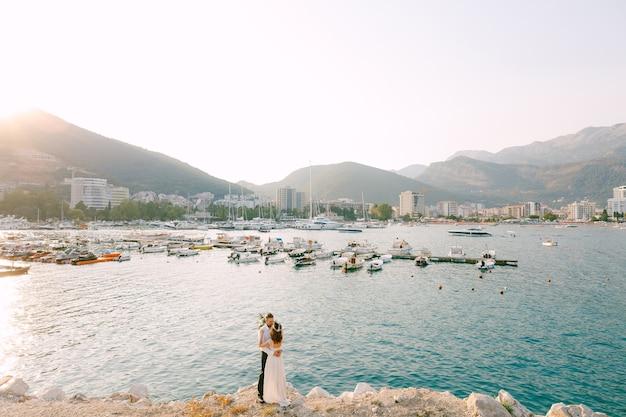 Die braut und der bräutigam umarmen und küssen am strand vor dem hintergrund des bootsanlegers in budva.
