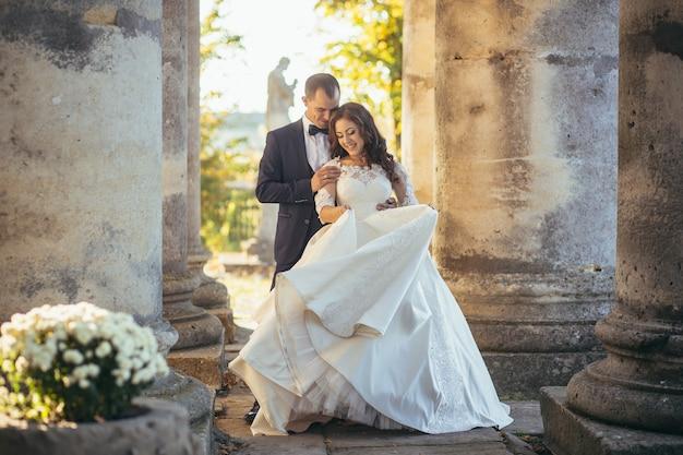 Die braut und der bräutigam umarmen und lächeln bei sonnenuntergang vor dem hintergrund der alten säulen!