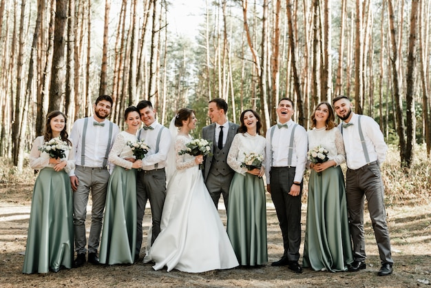 Die braut und der bräutigam und ihre freunde haben spaß und umarmen sich