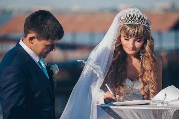 Die braut und der bräutigam unterzeichnen das dokument
