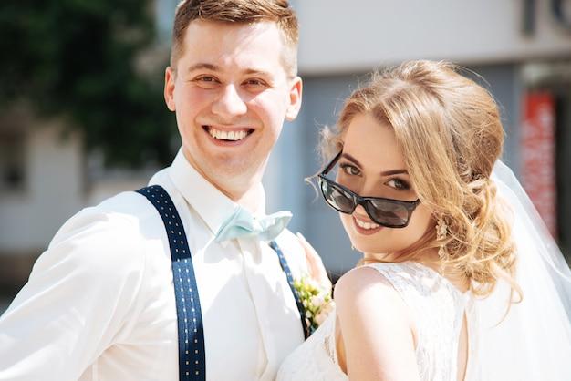 Die braut und der bräutigam werfen für die kamera auf