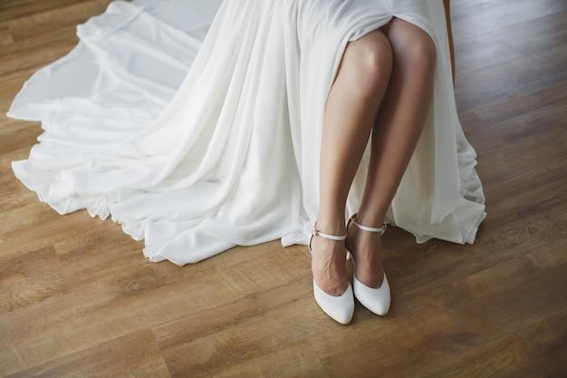 Die braut zieht weiße schuhe an den füßen an