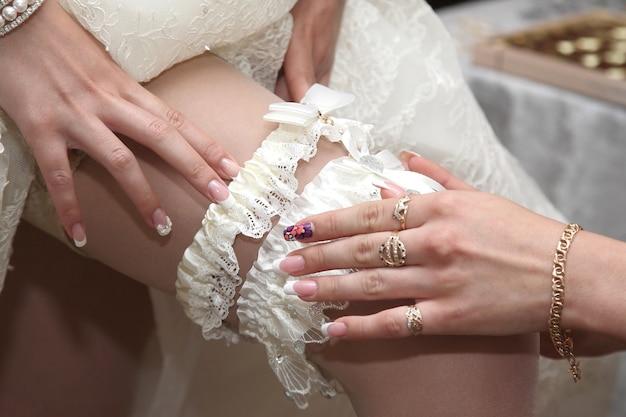 Die brautjungfer hilft, ein hochzeitsstrumpfband zu tragen. mode- und schönheitsfrauen