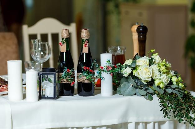 Die breite weiße kerze und zwei grüne flaschen mit rotwein, dekoriert mit blumengrün und schnur