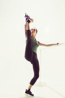 Die brünette athletische frau, die mit gummiband trainiert