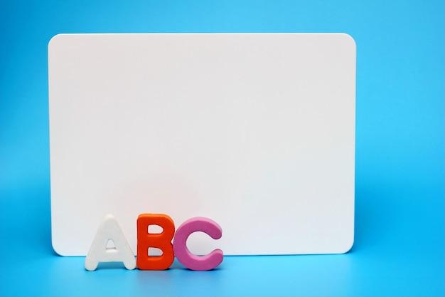 Die buchstaben des englischen alphabets in der nähe der weißen tafel.