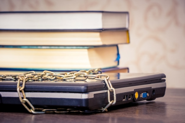 Die bücher liegen auf einem laptop, der durch eine kette verbunden ist