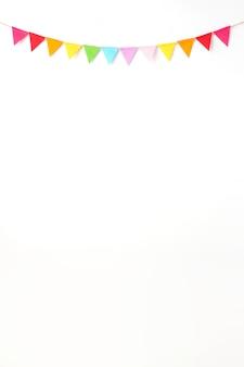Die bunten parteiflaggen, die am weißen wandhintergrund, geburtstag, jahrestag hängen, feiern b