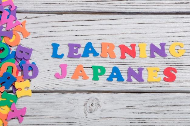 Die bunten wörter japanes machten mit bunten buchstaben über weißem holzbrett