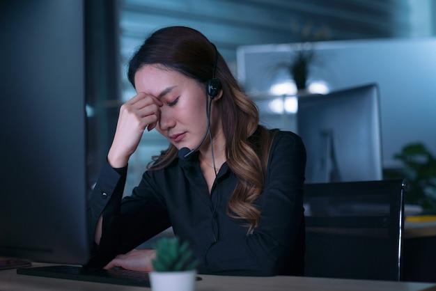 Die callcenter-geschäftsleute der thailändischen asiatischen frauen bekommen kopfschmerzen und migräne, wenn sie spät in der nacht arbeiten