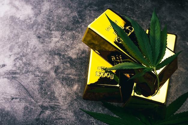 Die cannabispflanze mit goldbarren. goldbarren mit marihuanablättern.