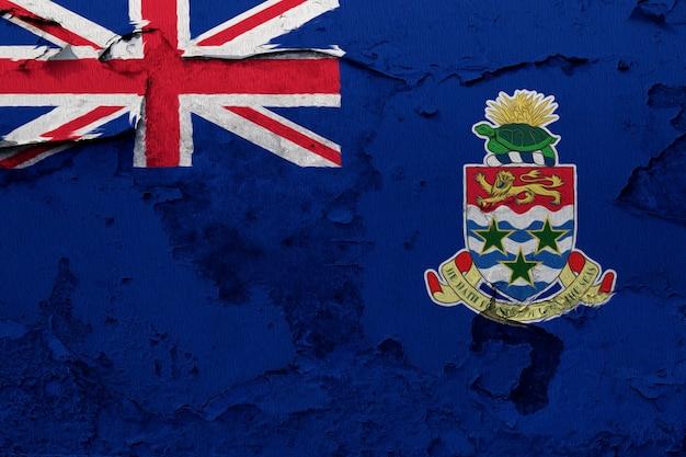 Die cayman islands-flagge, die auf schmutz gemalt wurde, riss wand