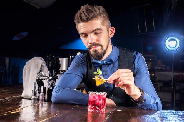 Die charmante barkeeperin kreiert einen cocktail in der kneipe
