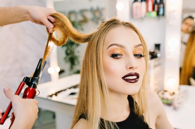 Die charmante blonde frau des nahaufnahmeporträts bereitet sich auf feier, party im schönheitssalon vor. stilvolles make-up, frisur, rote lippen, luxus-look, zufriedenheit, modisches modell