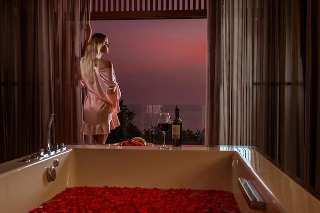 Die charmante blondine bereitet sich auf ein bad mit rosenblättern vor und trinkt champagner