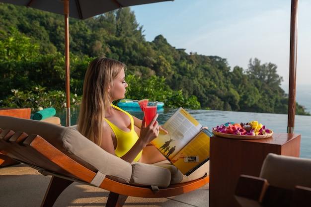 Die charmante blondine entspannt sich auf einer sonnenliege in der nähe des infinity-pools und trinkt einen wassermelonen-smoothie. ruhe in tropischen ländern. natürliche landschaft