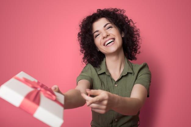 Die charmante brünette dame lächelt, während sie im studio eine geschenkbox erhält, die gut auf einer roten wand verpackt ist