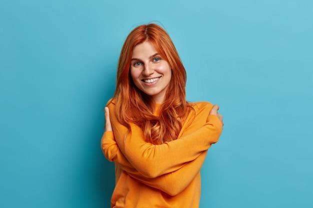 Die charmante, erfreute rothaarige europäerin umarmt ihren eigenen körper, gekleidet in ein lässiges orangefarbenes pulloverlächeln, fühlt sich angenehm wohl.