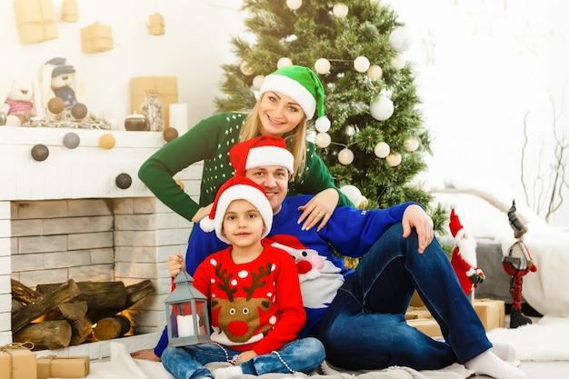 Die charmante familie sitzt in der nähe von weihnachtsbaum