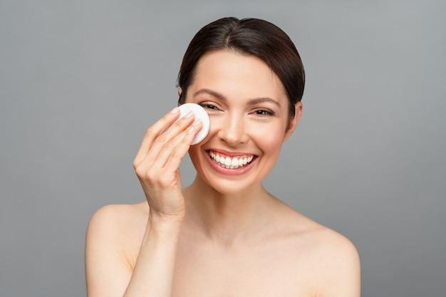 Die charmante frau lächelt. eine natürliche frau mit guter haut reinigt ihr gesicht mit einem wattepad. spa, kosmetik, schönheit