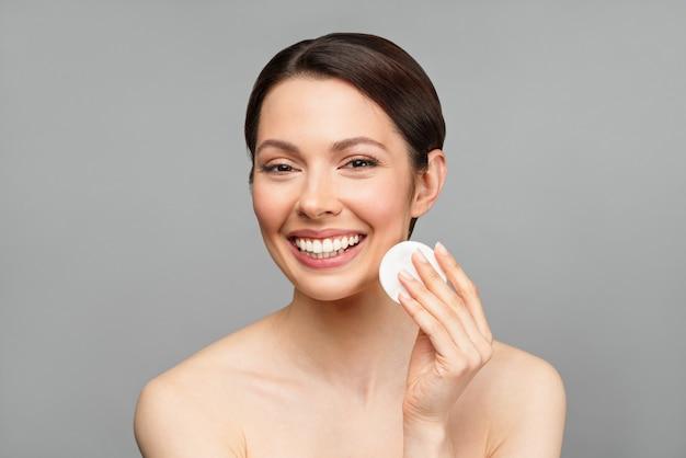 Die charmante frau lächelt eine natürliche frau mit guter haut reinigt ihr gesicht mit einem wattepad-spa