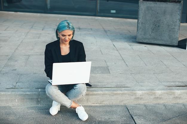 Die charmante freiberuflerin mit den blauen haaren sitzt auf der straße und arbeitet an ihrem computer