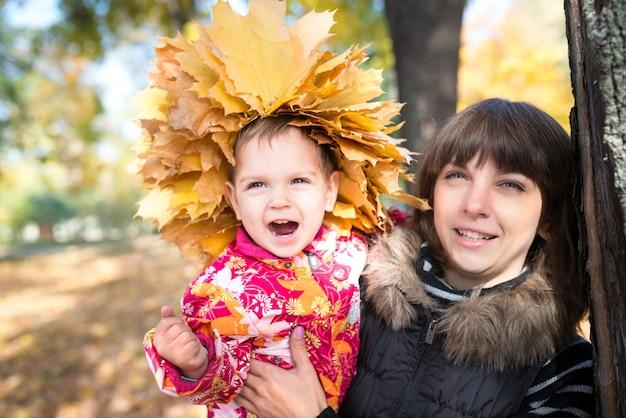 Die charmante junge mutter hält ein hübsches kleines mädchen mit einem kranz aus gelbem ahorn-herbstlaub auf dem kopf in den armen, während sie im park spazieren geht. herbstkonzept