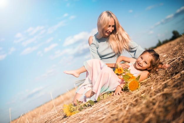 Die charmante junge mutter hat spaß mit ihrer kleinen tochter, die an einem warmen, sonnigen sommertag auf einem feld mit sonnenblumen sitzt
