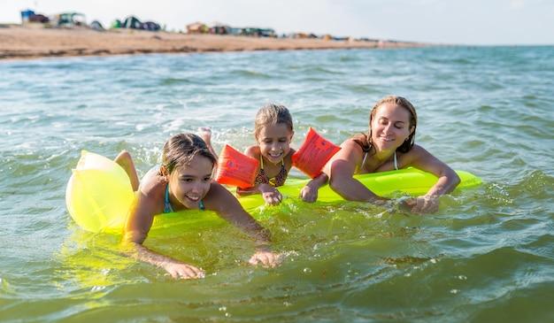 Die charmante junge mutter schwimmt an einem warmen sommertag mit ihren beiden glücklichen kleinen töchtern auf einer luftmatratze im see