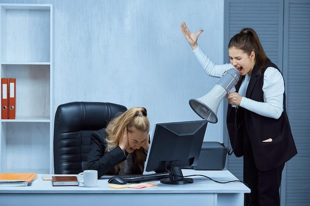 Die chefin, die einen lautsprecher in der hand hält, schreit ihren faulen untergebenen an, der am tisch sitzt