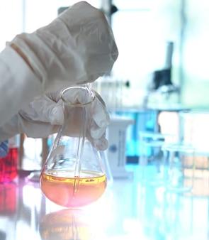 Die chemie, die mit gelbem flüssigem laborglas arbeitet