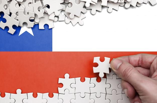 Die chile-flagge ist auf einem tisch abgebildet, auf dem die menschliche hand ein puzzle weißer farbe faltet