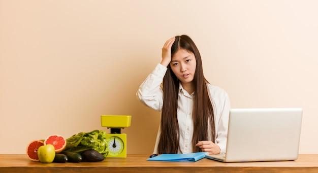 Die chinesische frau des jungen ernährungswissenschaftlers, die mit ihrem laptop arbeitet, ermüdete und sehr schläfrig, hand auf seinem kopf halten.
