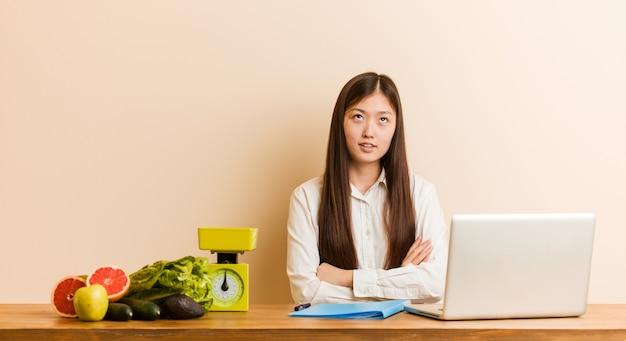 Die chinesische frau des jungen ernährungswissenschaftlers, die mit ihrem laptop arbeitet, ermüdete von einer sich wiederholenden aufgabe