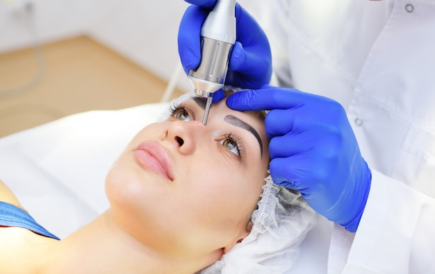 Die chirurgenkosmetikerin entfernt pigmentflecken und gefäßnetze auf der haut des patienten