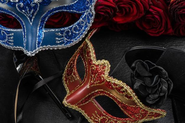 Die colombina, rote, blaue karnevals- oder maskerademasken. rosetten und schuhen mit hohen absätzen.
