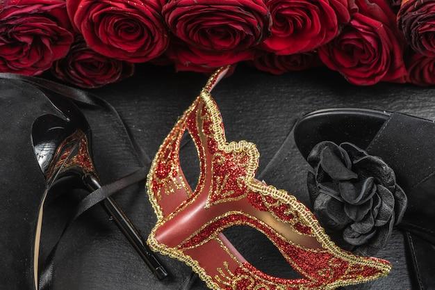 Die colombina, rote karnevals- oder maskerademaske. rosen- und absatzschuhe.