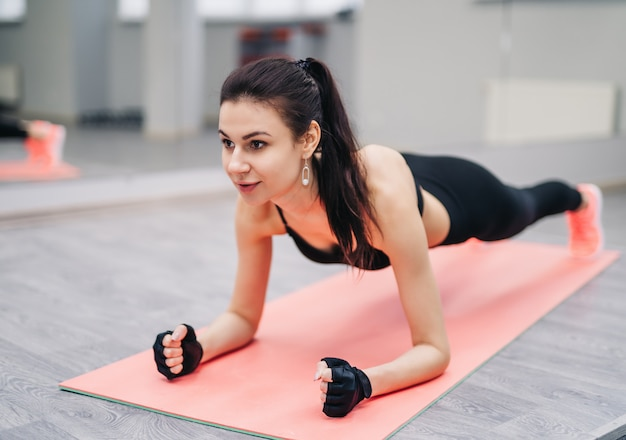 Die crossfit-frau, die liegestütze tut, trainiert mit den ellbogenunterarmen auf einer rosa matte in der turnhalle.