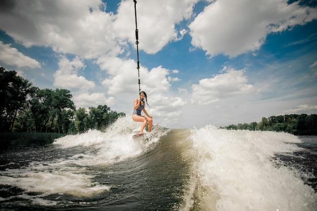 Die dame wird mit einem wakeboard hinter einem motorboot per kabel gezogen