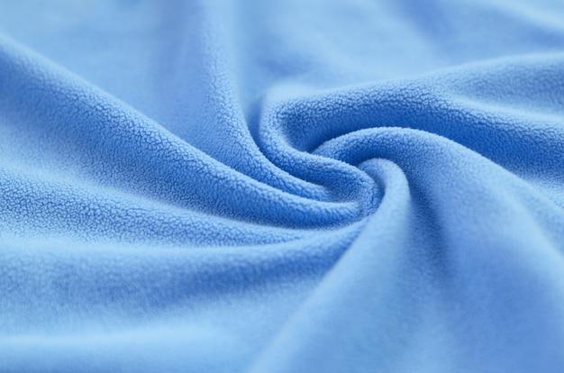Die decke aus pelzigem blauem fleece. ein hintergrund des hellblauen weichen plüschfleece