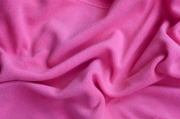 Die decke aus pelzigem pinkem fleece. ein hintergrund des hellrosa weichen plüschfleece-materials