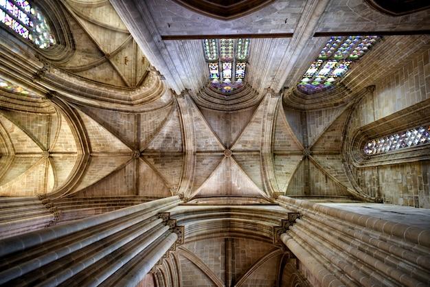 Die decke im inneren einer historischen kathedrale mit bögen und buntglasfenster