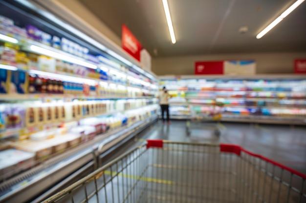 Die defokussierte unschärfe von weiblichen getränken, die milchprodukte kaufen, die beim einkaufen im supermarkt auf ein regal gestellt werden.