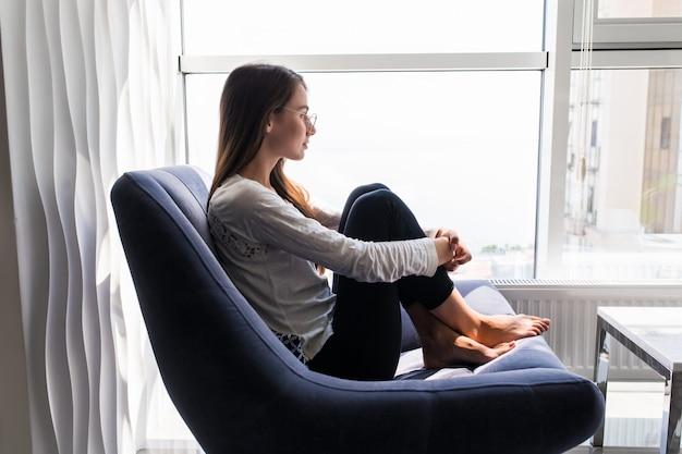 Die depressionsfrau sitzt zu hause auf dem stuhl