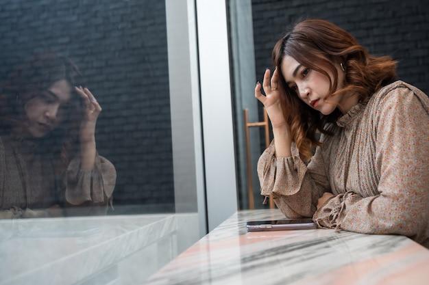 Die deprimierte frau, die kopfschmerzen hat, traurig sich fühlt, sorgen sich um problem