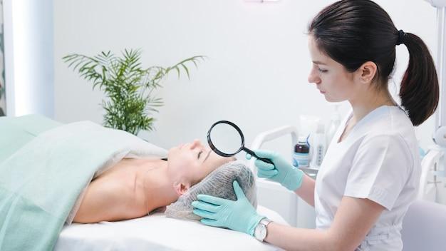 Die dermatologin untersucht das gesicht eines jungen patienten mit einer lupe in der klinik